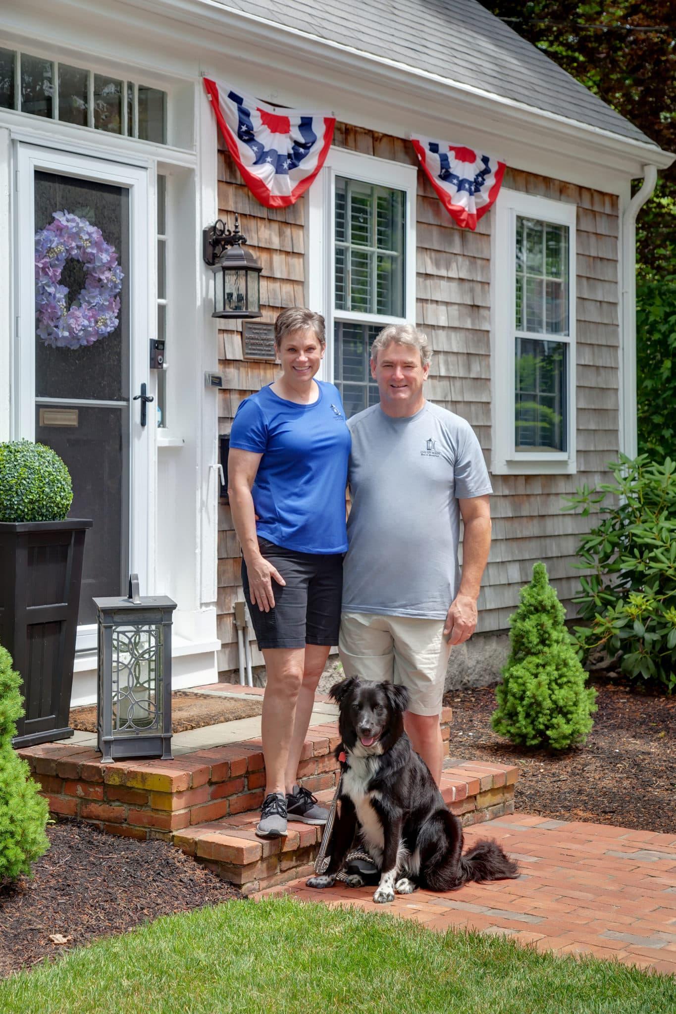 Portrait of Innkeepers Sarah Bradburn, Chris Kennedy and Crocker the dog on the front steps of the Inn on Main