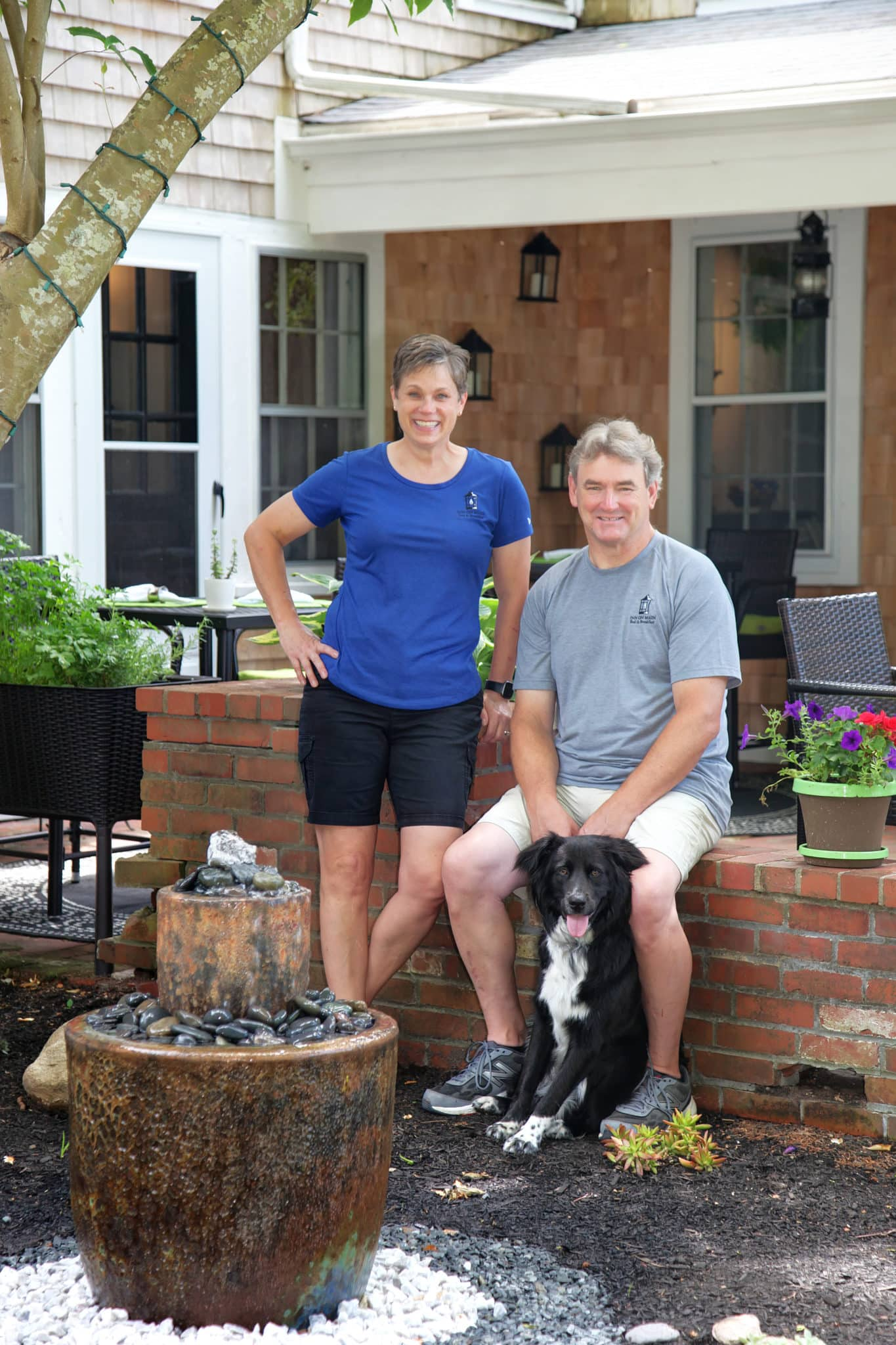 Innkeepers Sarah Bradburn, Chris Kennedy and Crocker the dog outside by the patio brick wall behind the water fountain