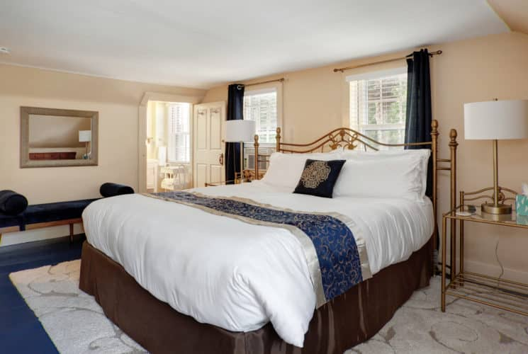View of the Sleep number California King bed in the Nantucket guest room. End tables, lamps, wall mirror, settee, and area rug
