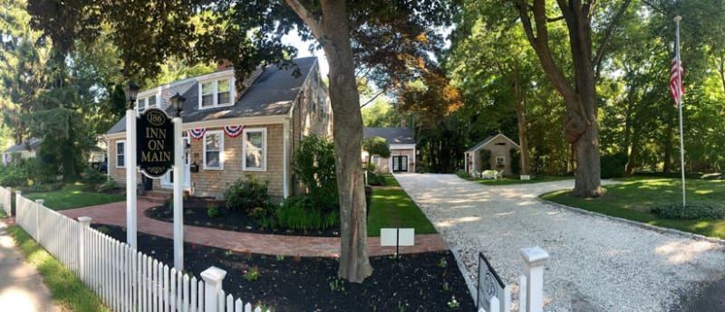 Exterior view of inn with light cedar shingle siding, white trim, vegetation, and light colored gravel driveway