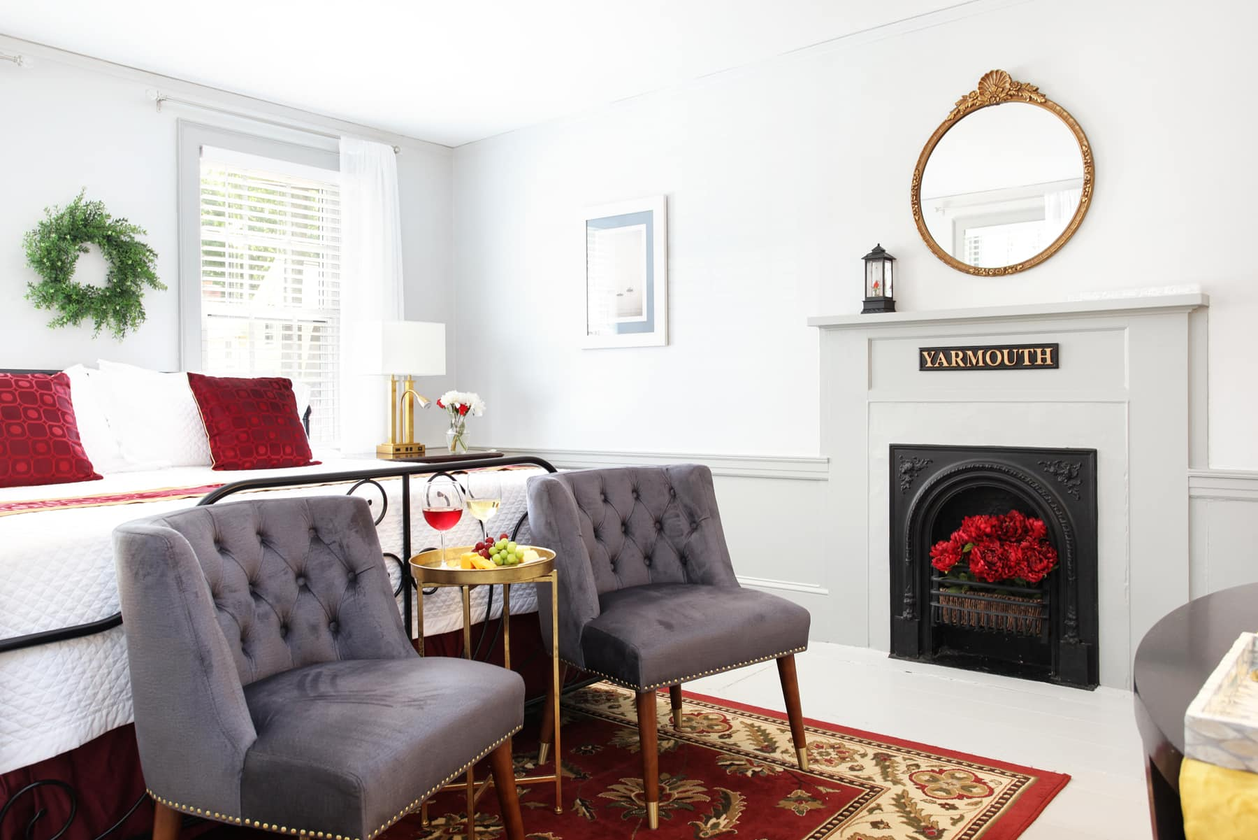 Bedroom with white bedding and red blanket, red upholstered chair, and red and gold rug