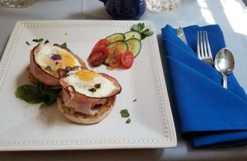 White China plate with English muffin topped with ham and eggs and tomatoes and cucumbers on the side