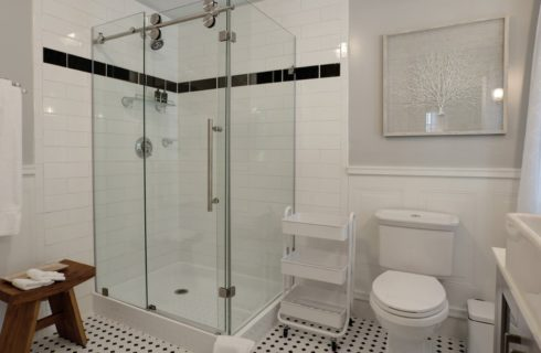 Bathroom with white and black tiled shower, white toilet and sink, and black and white tiled flower