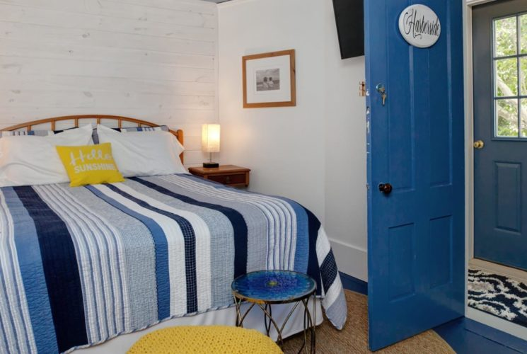 Bedroom painted white with dark blue painted wooden floors with light brown wooden headboard, light and dark blue striped quilt with yellow pillow, and white and brown nightstands